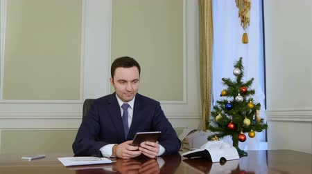 nákrčník : Successfull businessman using a tablet to send E-mail congratulation over the Internet Dostupné videozáznamy