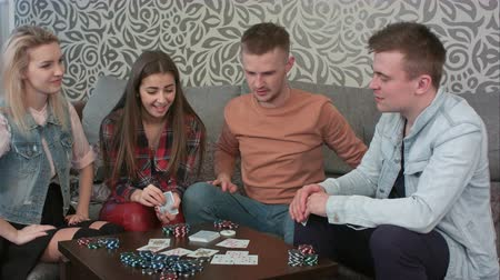 croupier : Group of teens finishing poker game, opening their cards and recognizing the winner