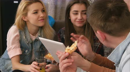 подростковый возраст : Student company eating pizza and using tablet at home