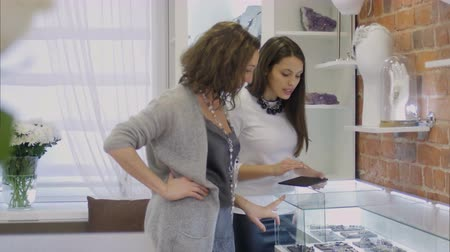 exibindo : Attractive woman and female seller consultant looking on jewellery through the showcase