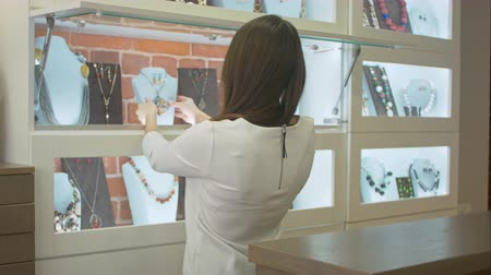 bijouterie : Young attractive shopassistant looking on the showcase in jewelry shop Stock Footage