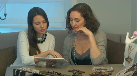 talk show : Young female seller and attractive woman select jewellery using tablet sitting on comfortable sofa in a jewelry store