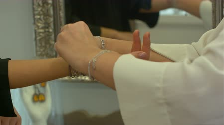 nobel : Woman tries on expensive bracelet in a jewelry store