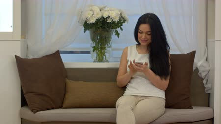 astonishment : Attractive young woman chatting and texting messages on mobile phone sitting on sofa Stock Footage