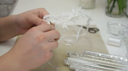 azték : Woman hands needle sewing white beads for hair accessory