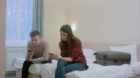 veszekedés : Couple sitting on the bed, not talking to each other after quarrel, typing on smartphones Stock mozgókép