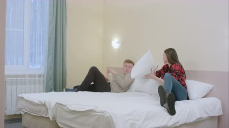 poduszka : Pretty girl disturbs her boyfriend, while he was reading and the couple start to fight with pillows Wideo