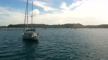 sail rock : Copter fly over the yacht moored in a bay near rock Stock Footage