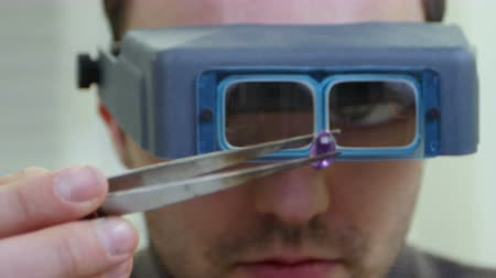 appraisal : Master jeweler in special glasses looking at gem Stock Footage