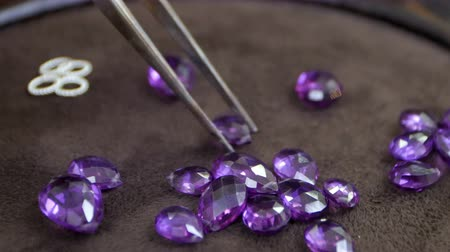 appraisal : Gems being held by a tweezer on the desk