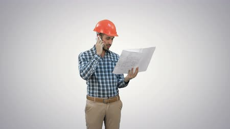 bossy : Site manager talking on the phone holding blueprints on white background. Stock Footage