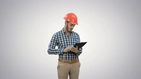 supervising : Young engineer in helmet inspecting construction site on white background.