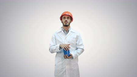 deconstruction : Engineer in helmet and white coat launching demolition on white background. Stock Footage