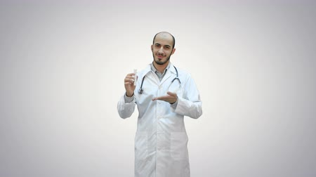 предназначенный только для мужчин : Smiling doctor in uniform pointing at medicine bottle and looking at camera on white background.