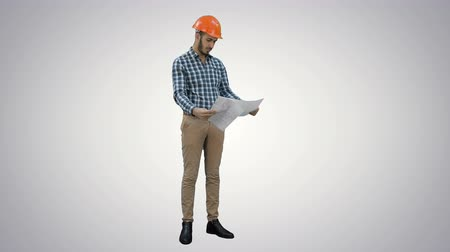 supervising : Engineer in hardhat examining construction plan on white background. Stock Footage