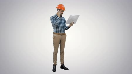 bossy : Site manager talking on mobile phone holding blueprints on white background.