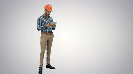 workman : Engineer using a wireless tablet to check construction project on white background. Stock Footage
