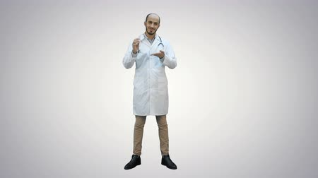 болеутоляющее : Smiling doctor in white coat pointing at medicine bottle and looking at camera on white background.