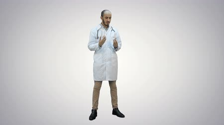 болеутоляющее : Male doctor describing two different pills on white background.