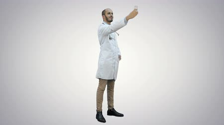 medics : Smiling doctor in white coat taking selfie on his phone on white background.