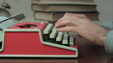 költő : Mans hands typing on a red typewriter Stock mozgókép