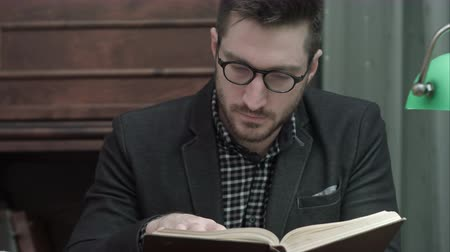 scholar : Young academic in glasses attentively reading a book