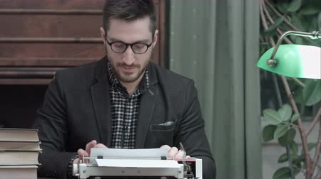 поэт : Young author in glasses rubbing his hands and starting typing on a red vintage typewriter