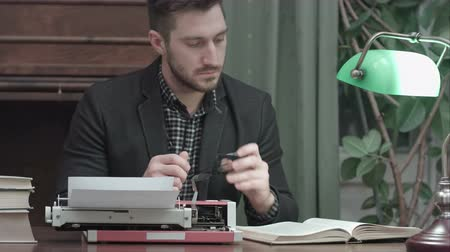 поэт : Serious young man with glasses sitting at the desk with typewriter and reading book