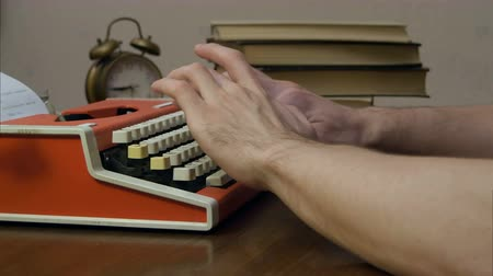 költő : Mans hands typing on a red retro typewriter