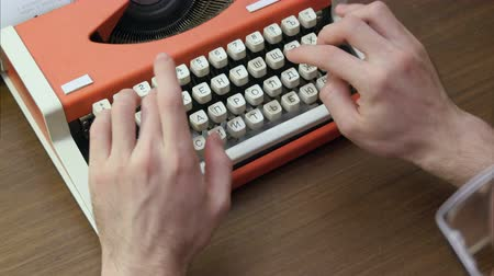 поэт : Mans hands typing on an old red mechanical typewriter