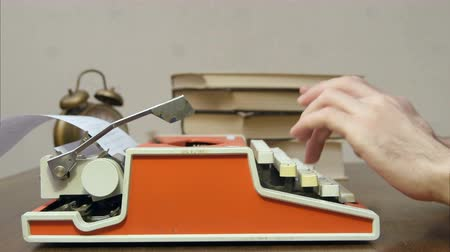 поэт : Mans hands typing on a red retro typewriter on a table with books Стоковые видеозаписи