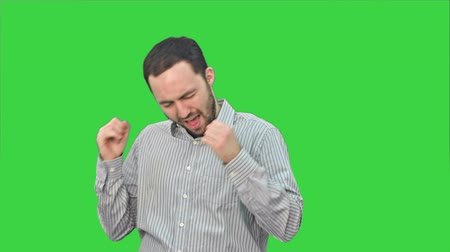 exited : Bearded young man happily dancing and singing on a Green Screen, Chroma Key.
