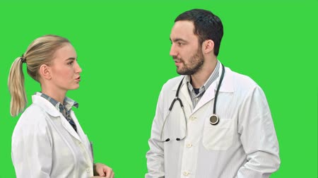 atender : Two medical professionals discuss with a patient on a Green Screen, Chroma Key.