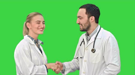 anlaşma : Young man doctor and beautiful nurse shaking hands after successful operation and looking at camera on a Green Screen, Chroma Key.