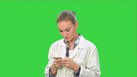 sending : Female doctor using texting messages using modern smartphone and smiling on a Green Screen, Chroma Key.
