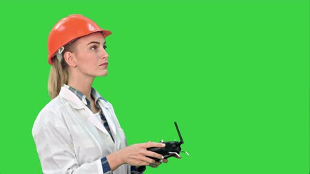 striker : Female construction worker operating a crane using remote control on a Green Screen, Chroma Key.