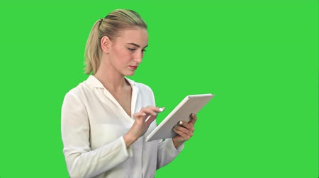 тачпад : Concentrated businesswoman standing with digital tablet on a Green Screen, Chroma Key.