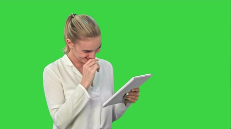 estrondo : Beautiful young woman laughing while looking at digital tablet on a Green Screen, Chroma Key. Stock Footage