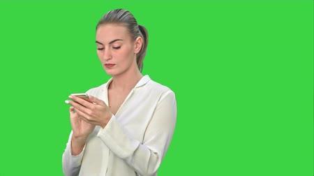 kommunikátor : Pensive business woman using mobile cell phone reading message, wear white suit on a Green Screen, Chroma Key.