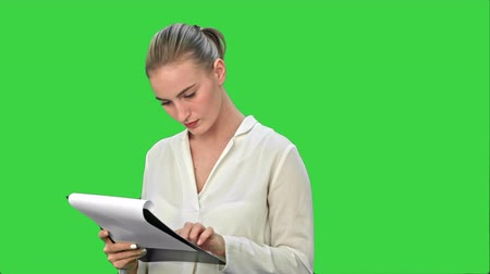 colarinho branco : Young businesswoman reading documents on a Green Screen, Chroma Key. Stock Footage
