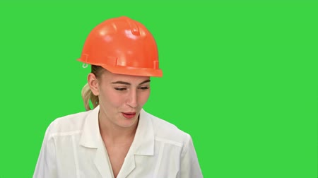 exited : Young female construction engineer smiling while have a video conference with laptop on a Green Screen, Chroma Key. Stock Footage
