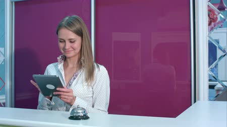 lobby : Smiling female receptionist with tablet welcoming hotel guests