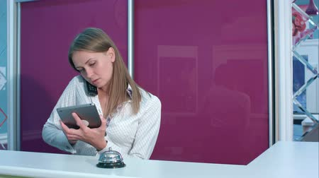 liga : Busy female receptionist taking a phone call while holding tablet behind the counter in a hotel lobby Vídeos