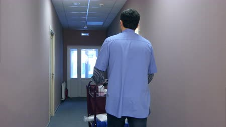 lavanderia : Young man pushing a housekeeping cart with clean towels in a hotel Stock Footage