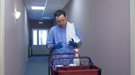 keeper : Male hotel cleaner putting on gloves before cleaning the room