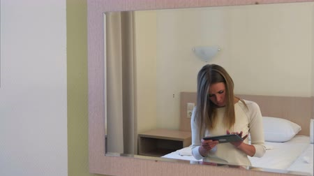 targi : Young blonde woman using tablet sitting on the bed in hotel room Wideo