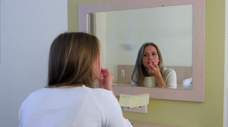 румяна : Young woman putting makeup while looking in the mirror at hotel room