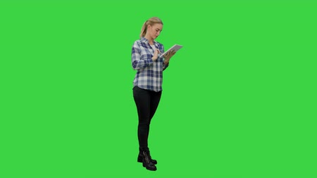 cortiça : Young woman standing on green background with digital tablet on a Green Screen, Chroma Key.