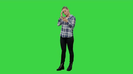 osobowość : Tired working young woman reading messages on the phone on a Green Screen, Chroma Key. Wideo