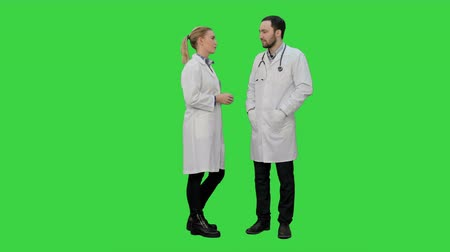 speach : Two professional doctors talk before operation on a Green Screen, Chroma Key.